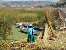 Kvinna nära hennes familjfartyg på en av Uros'ens öar - sjö Titicaca Arkivbild