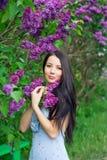 Kvinna nära lilorna royaltyfria bilder