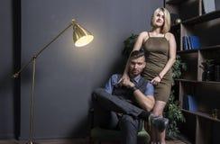Kvinna nära med den lyckade rikeman Ung lyckad affärsman i stol och hans sexiga kvinna i klänning i lyxig lägenhet Arkivfoton