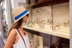 Kvinna nära ställa ut med klockor Royaltyfri Foto