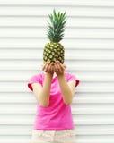 Kvinna och ananas på hennes head anseende över vit Arkivfoton