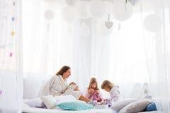 Kvinna och barn på säng Royaltyfri Fotografi