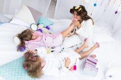 Kvinna och barn på säng Royaltyfria Bilder