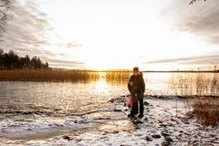 Kvinna- och barnanseende på en kall djupfryst strand med snö Härlig guld- vinterlandskapsolnedgång över lugna vatten mot havet royaltyfri fotografi