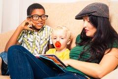 Kvinna och barnavläsningsbok Arkivfoton