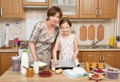 Kvinna- och barnflicka som förbereder mjöl för att baka och kakor på en träbakgrund Råkost och köksgeråd Bryt ett ägg, c Arkivbild