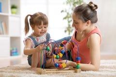 Kvinna- och barnlek i barnkammare arkivbilder