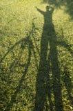 Kvinna och cykel-skugga. Arkivfoto