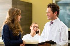Kvinna och doktor på mottagandet av kliniken arkivfoton