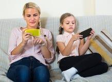 Kvinna och dotter med smartphones Arkivfoto