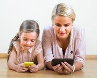 Kvinna och dotter med smartphones Royaltyfria Bilder