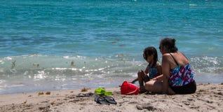 Kvinna och dotter på stranden arkivbilder