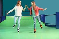 Kvinna och dotter som har gyckel på den åka skridskor isbanan för rulle royaltyfri fotografi