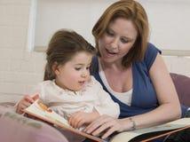 Kvinna och dotter som ser bilderboken Arkivbilder