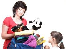 Kvinna- och dotterhanden proppade mycket av kläder och skuldrapåse Royaltyfri Foto
