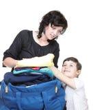 Kvinna- och dotterhanden proppade mycket av kläder och skuldrapåse Arkivbilder