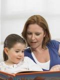 Kvinna- och dotterläsebok hemma Royaltyfria Foton