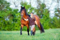 Kvinna och en häst som går i fältet Arkivfoto