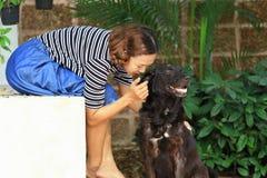 Kvinna och en hund i trädgården Arkivfoto