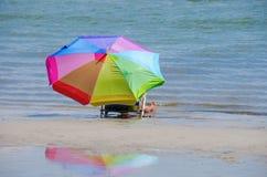 Kvinna och färgrikt paraply vid shorelinen Arkivfoto