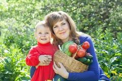 Kvinna och flicka med grönsaker   i trädgård Royaltyfri Bild