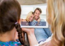 Kvinna och flicka som har en video appell med par på den digitala minnestavlan Arkivbild