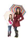 Kvinna och flicka som rymmer färgrika paraplyer Royaltyfri Bild