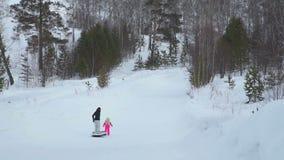 Kvinna och flickan som klättrar en kulle med snöröret stock video