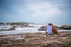 Kvinna och golden retriever på stranden royaltyfri bild