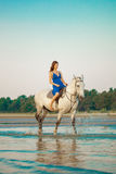 Kvinna och häst på bakgrunden av himmel och vatten Flickamodellnolla arkivfoton