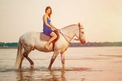 Kvinna och häst på bakgrunden av himmel och vatten Flickamodellnolla fotografering för bildbyråer