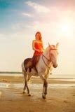 Kvinna och häst på bakgrunden av himmel och vatten Flickamodellnolla royaltyfria bilder