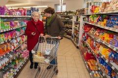Kvinna och hög kvinna som går för att shoppa i supermarket royaltyfria foton