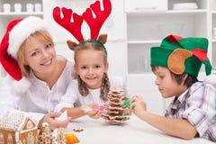 Kvinna och henne ungar som dekorerar julkakor Arkivbild