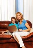 Kvinna och hennes barn med bärbara datorn på soffan royaltyfria bilder