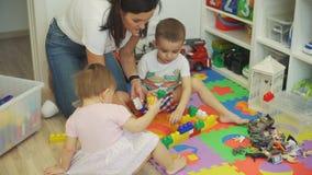 Kvinna och hennes barn som spelar konstruktörn lager videofilmer