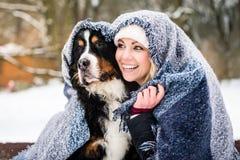 Kvinna och hennes hund som får varma på kall vinterdag under en blanke royaltyfria foton