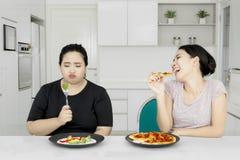 Kvinna och hennes syster med pizza Royaltyfria Bilder