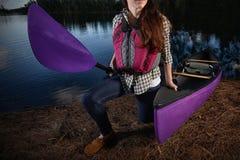 Kvinna och kajak på sjön i nedgången Royaltyfri Foto