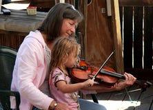 Kvinna och liten flicka som spelar fiolen på akustisk musikfestival i Florida arkivfoton