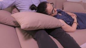 Kvinna och män som kopplar av på soffan nära TV arkivfilmer