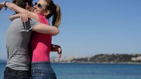 Kvinna och make vid havet som kramar och kysser lager videofilmer