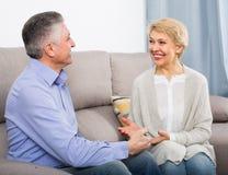 Kvinna och man 51-56 år vänligt samtal för gammal förälskelse Arkivbild