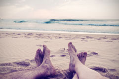 Kvinna och man (ben och foten) i stranden, tappningstil Arkivfoto