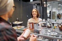 Kvinna och man eller bartender med kaffekoppen på kafét Arkivfoton