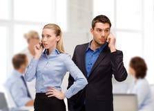Kvinna och man med mobiltelefoner att kalla Arkivfoto