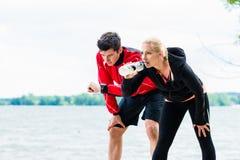 Kvinna och man på avbrottet från att köra framme av sjön Arkivfoto