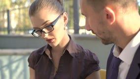Kvinna och man som arbetar med minnestavlan på den utomhus- bänken 4K arkivfilmer