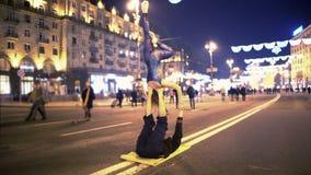 Kvinna och man som gör akrobatiska jippon i centret, aftontid, extrem hobby arkivfilmer