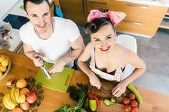 Kvinna och man som klipper gr?nsaker f?r sallad arkivfoto